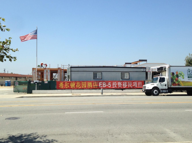 A banner promotes the EB-5 immigrant visa for investors at a hotel construction site in El Monte.