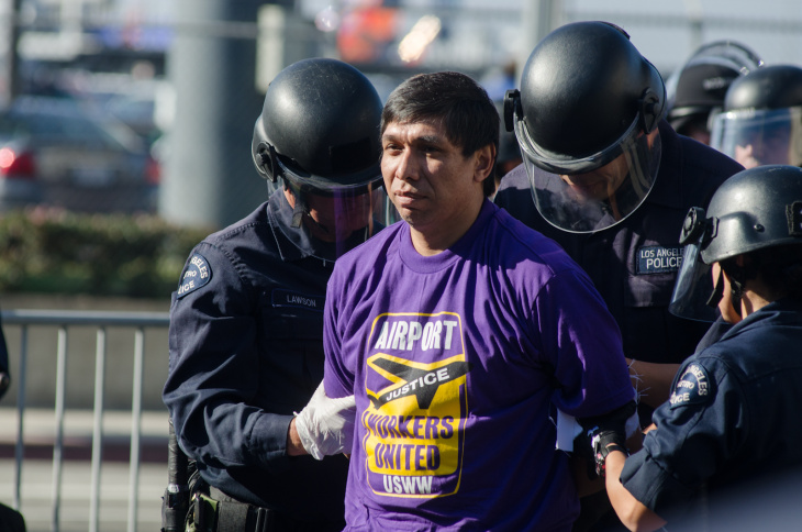 A member of USWW is apprehended after disobeying orders to disperse in Los Angeles, Calif., Wednesday, November 21, 2012. A total of 12 people were arrested in the march.