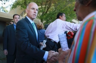 California attorney general and democratic gubernatorial candidate Jerry Brown (2nd L) greets a voter after voting on November 2, 2010 in Oakland, California. Jerry Brown is in a tight race to win the election for California governor against republican challenger and former eBay CEO Meg Whitman.