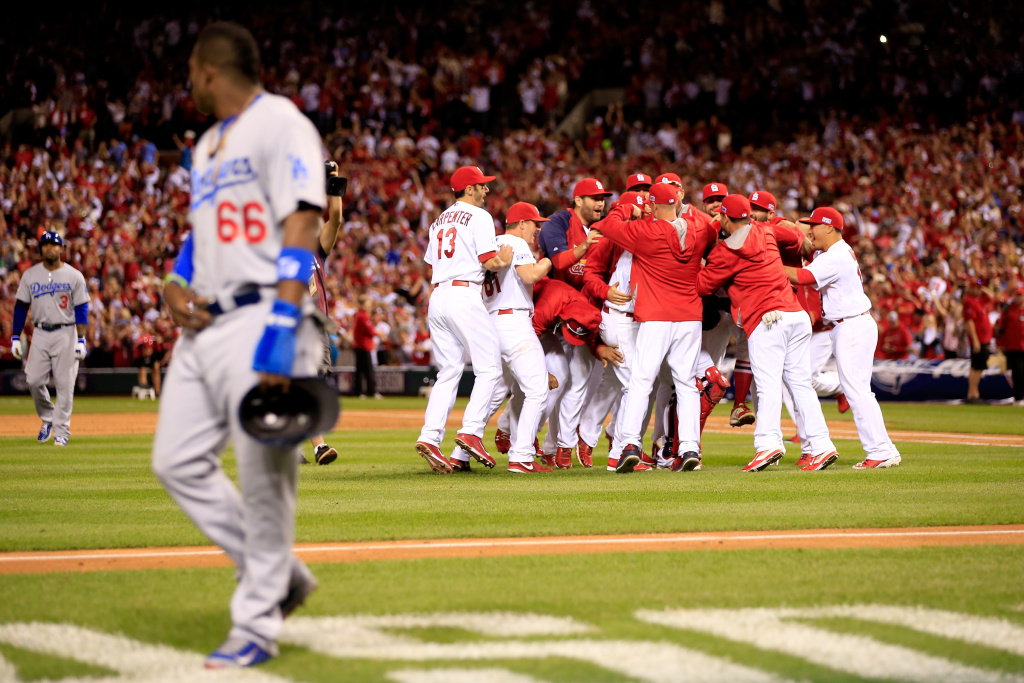 ST LOUIS, MO - OCTOBER 07:  The St. Louis Cardinals celebrate after defeating the Los Angeles Dodgers as Yasiel Puig #66 of the Los Angeles Dodgers walks off the field in Game Four of the National League Divison Series at Busch Stadium on October 7, 2014 in St Louis, Missouri.  (Photo by Jamie Squire/Getty Images)
