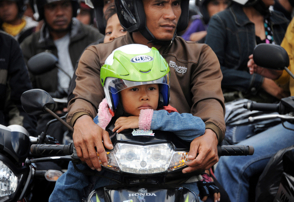 A young boy sits with his family on a motorbike as motorists wait to board a ferry headed for Java from the port of Gilimanuk in Jembrana on the mainly Hindu resort island of Bali on August 28, 2011.