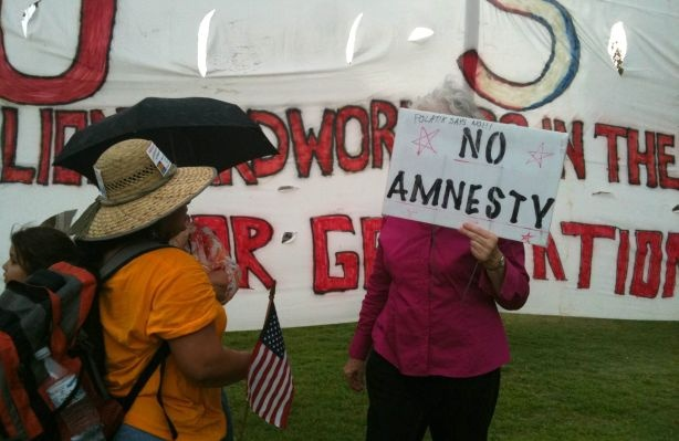 A supporter of SB 1070 engages in a conversation with Gloria Godoy, a Guatemalan American who came from Los Angeles to protest against Arizona's new immigration law.