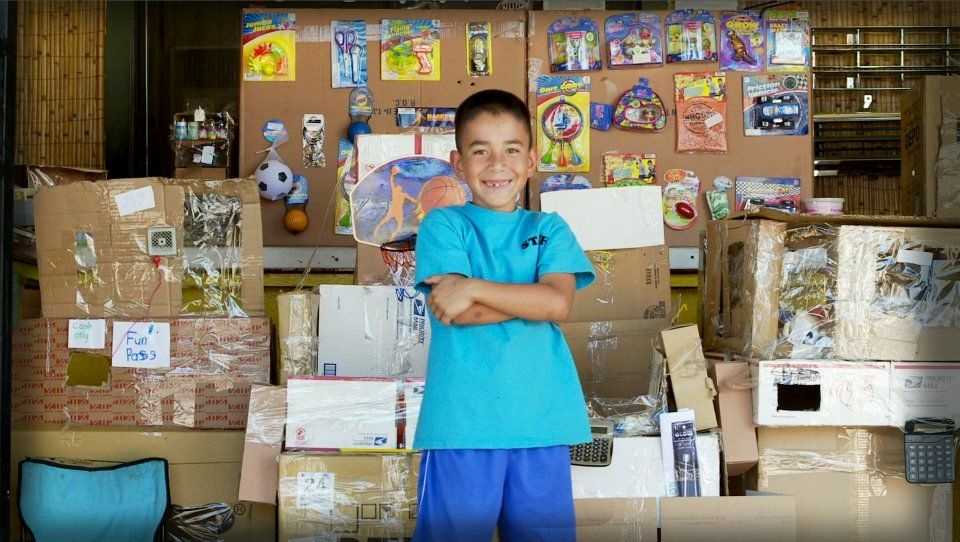 9-year-old Caine Monroy stands in front of his cardboard arcade at his dad's auto shop in East L.A.