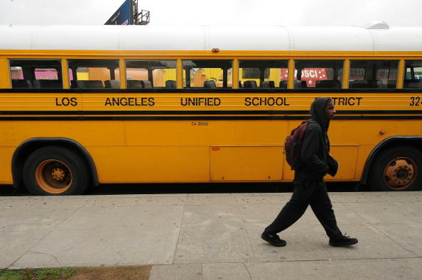 A student walks past a LAUSD school bus.