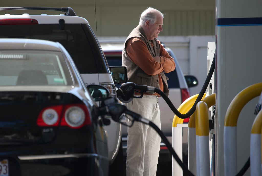A customer pumps gasoline into his car at an Arco gas station on March 3, 2015 in Mill Valley. A new report finds switching to an electric car can save hundreds every year on gasoline costs.
