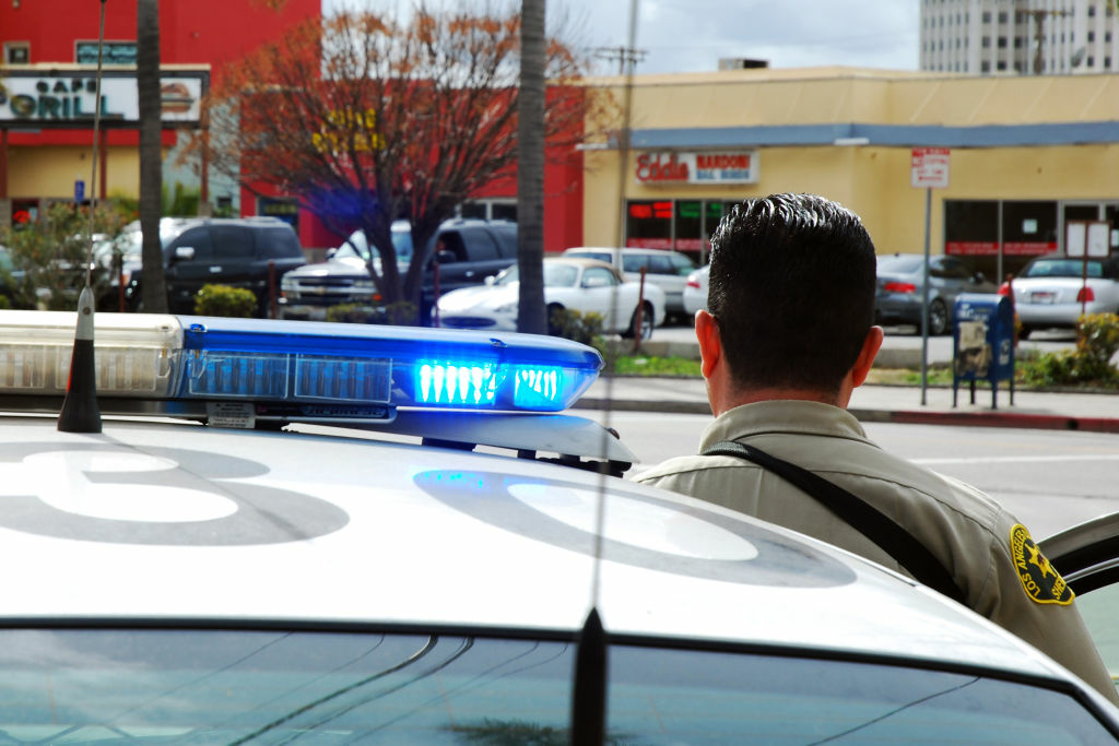 FILE: An officer from the Los Angeles County Sheriff's Department guards an intersection outside the Twin Towers Correctional Facility in L.A. on Feb. 8, 2013.