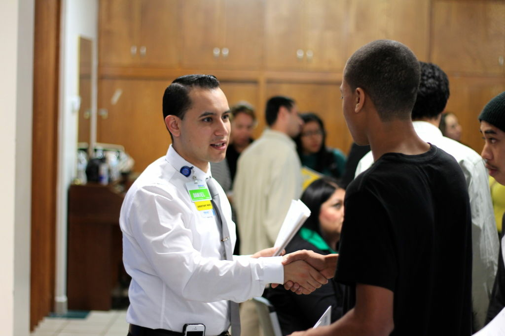 Daniel Vera, assistant manager at the Altadena Walmart Neighborhood Market, greets job seekers at the