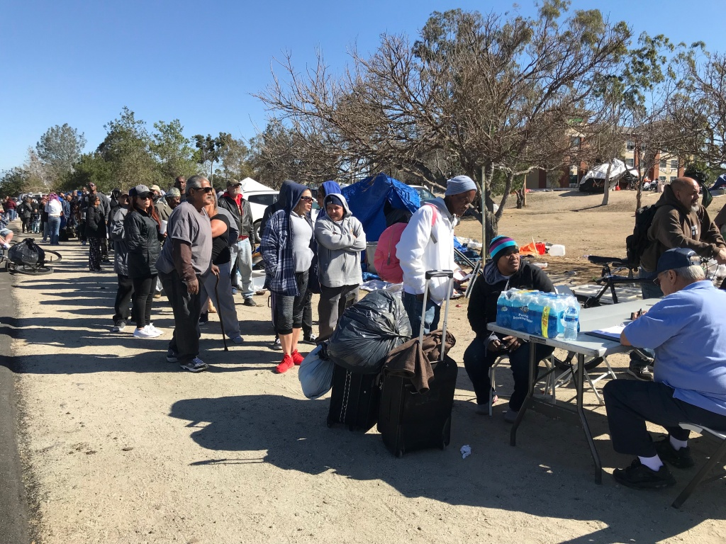 Homeless people living along the Santa Ana River flood control channel wait in line for motel vouchers offered by the county on Tuesday, Feb. 20, 2018.