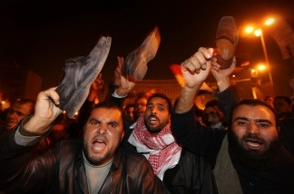 Anti-government protestors waves their shoes, in a gesture of anger, after President Hosni Mubarak announces that he will not seek re-election on Feb. 1, 2011 in Cairo, Egypt.