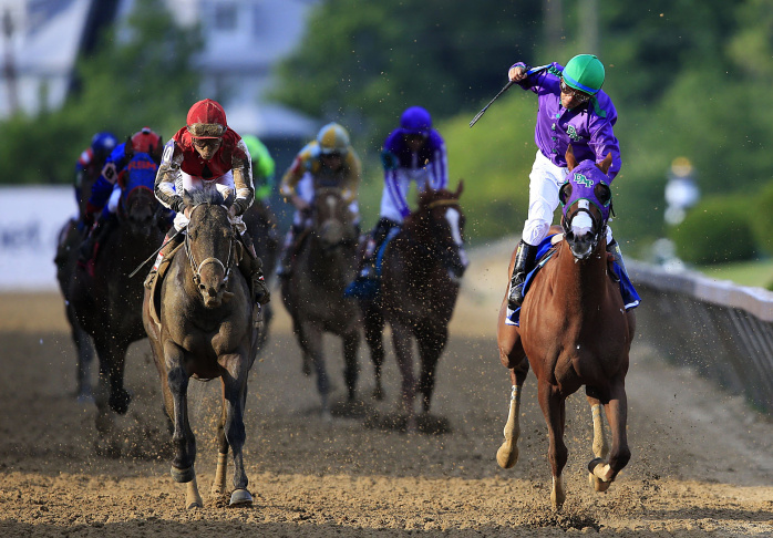California Chrome #3, ridden by Victor Espinoza, crosses the finishline to win the 139th running of the Preakness Stakes at Pimlico Race Course on May 17, 2014 in Baltimore, Maryland.