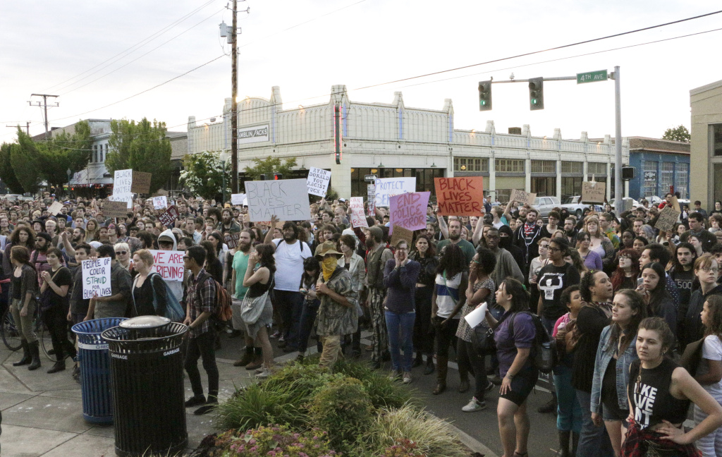 Hundreds of people protesting a police shooting gather outside of City Hall in Olympia, Wash., on Thursday. Police say that two stepbrothers suspected of trying to steal beer from a grocery store were unarmed when they were shot by a police officer who confronted them.