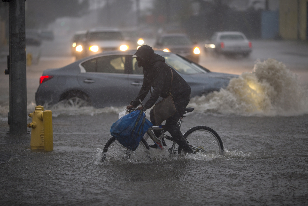 A bicyclist rides along a flooded street as a powerful storm moves across Southern California on February 17, 2017 in Sun Valley, California.