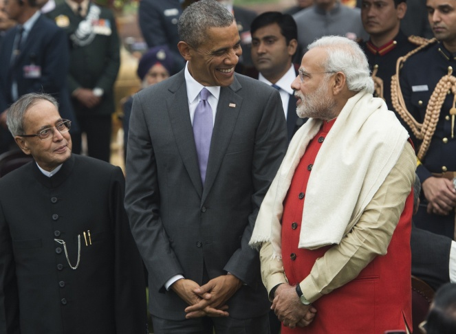 US President Barack Obama (2L) waves as he leaves India's Republic Day parade on Rajpath with Indian Prime Minister Narendra Modi (L) and Indian President Pranab Mukherjee (C) in New Delhi on January 26, 2015. Rain failed to dampen spirits at India's Republic Day parade January 26 as Barack Obama became the first US president to attend the spectacular military and cultural display in a mark of the nations' growing closeness.  AFP PHOTO / Roberto SCHMIDT        (Photo credit should read ROBERTO SCHMIDT/AFP/Getty Images)