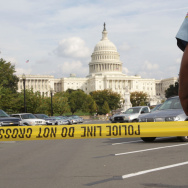 An officer stands just outside police tape Thursday as authorities investigate a car chase that began at the White House and ended near the Capitol.