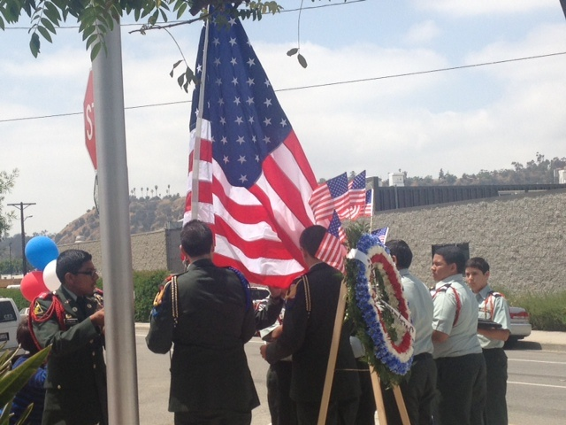 Veterans from the Marine Corp and Air Force salute the American flag during the singing of the national anthem during a Memorial Day ceremony held at the Cypress Park Veterans Memorial in the East Los Angeles.
