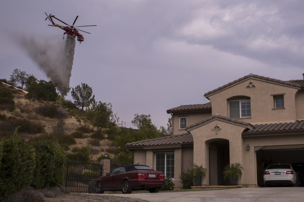 An S-64E Sikorsky Skycrane firefighting helicopter makes a drop to protect a house during the La Tuna Fire on September 3, 2017 near Burbank, California. The city requires people living in fire-prone areas to clear brush from 200 feet around their house.
