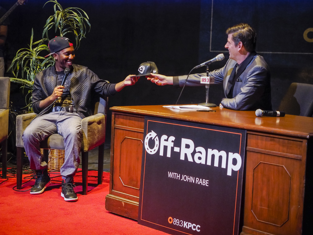 Comedian Chris Redd, who just moved to Los Angeles, receives a welcoming gift host John Rabe during Off-Ramp's 10th Anniversary special at the Los Angeles Theater Center in Downtown LA.
