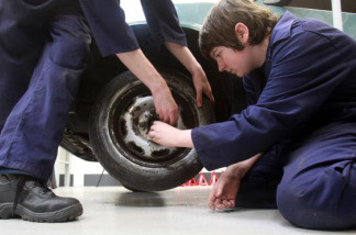 Students learn car mechanics at a school in England. California officials want to increase technical training for students to train them in careers that don't require college.
