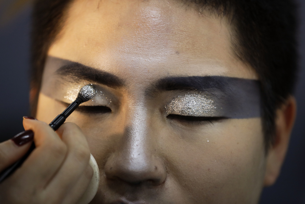 A makeup artist applies glitter to a performer backstage during the Opening Ceremony of the Pyeongchang 2018 Winter Olympics on February 9, 2018.