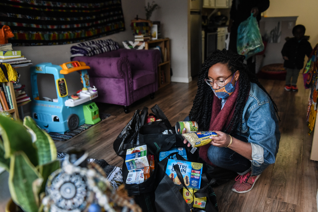 Mother looks at food and essential items that were delivered to her.