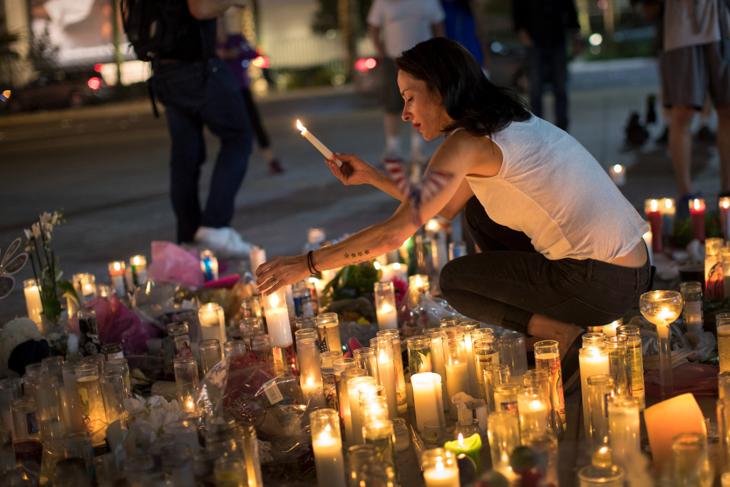Las Vegas resident Elisabeth Apcar lights candles at a makeshift memorial at the northern end of the Last Vegas Strip, October 4, 2017 in Las Vegas, Nevada.