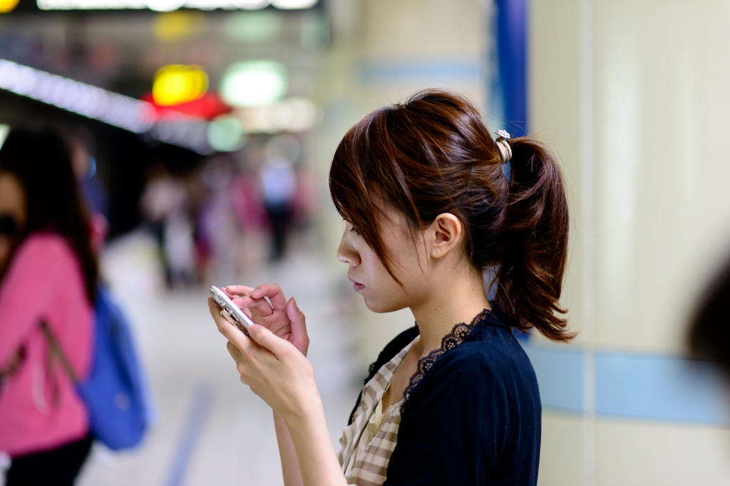 A woman is distracted by her cellphone while walking.