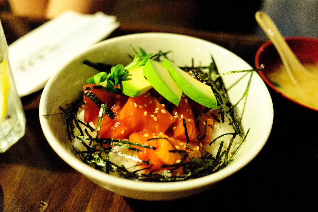 A poke bowl topped with avocado and seaweed.