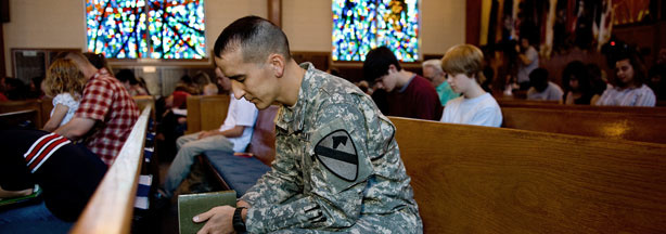US Army Chaplain 1st Lt. Joshua Remy prays alongside fellow parishoners as he attends non-denominational church services at Fort Hood's 1st Air Cavalry Divisional Memorial Chapel, November 8, 2009 in Killeen, Texas.