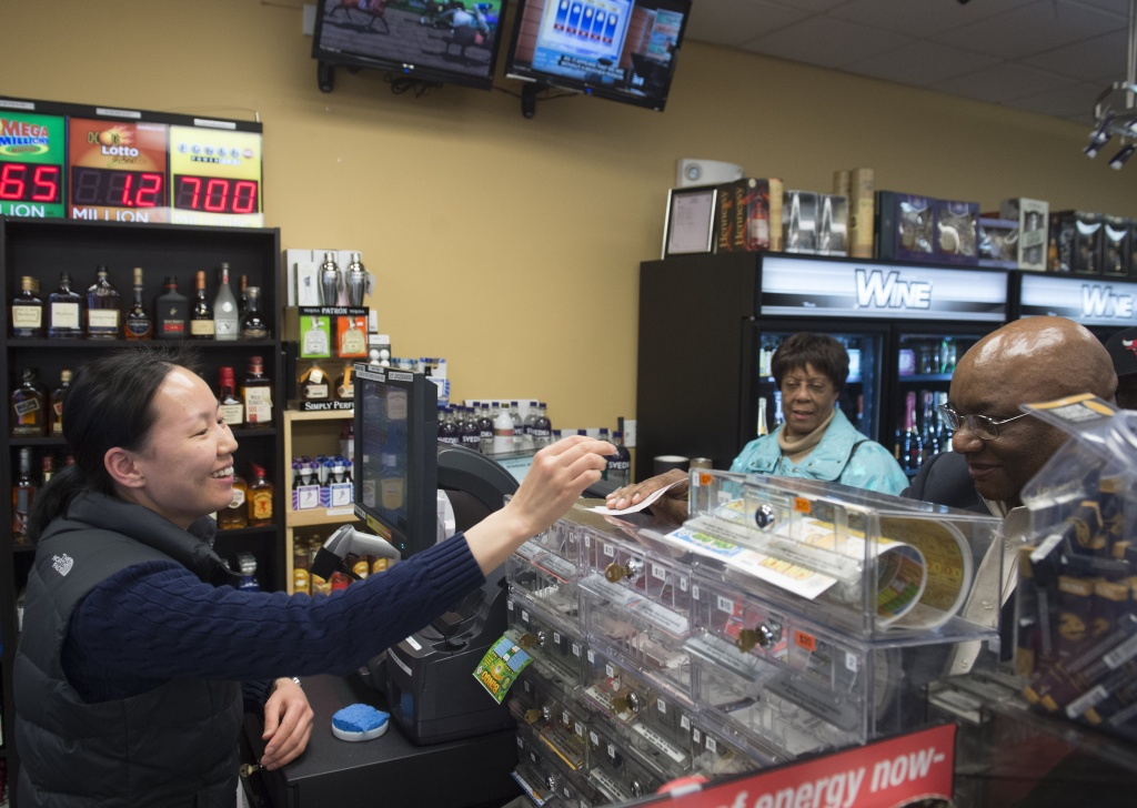 Ali Tsedev sells Powerball lottery tickets at a convenience store in Washington, DC on Jan. 7, 2016. Lottery officials predict Saturday's jackpot will reach $900 million, the largest in history.