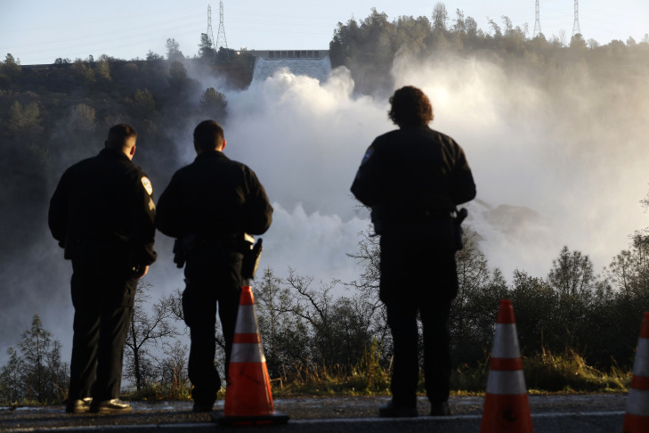 Police officers watch the Oroville Dam's main spillway from a lookout point Tuesday, Feb. 14, 2017, in Oroville, Calif. Crews working around the clock atop the crippled Oroville Dam have made progress repairing the damaged spillway, state officials said Tuesday.