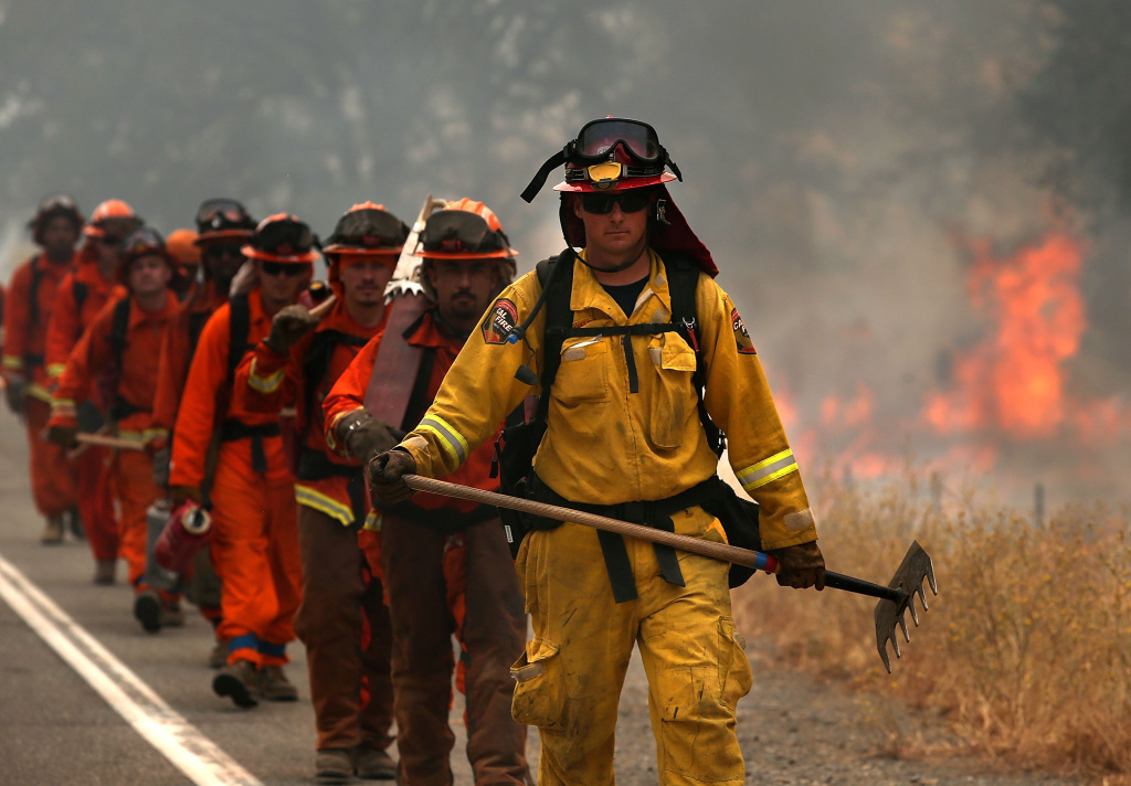 A Cal Fire firefighter leads a group of inmate firefighters during a burn operation to head off the Rocky Fire on August 2, 2015 near Clearlake, California.