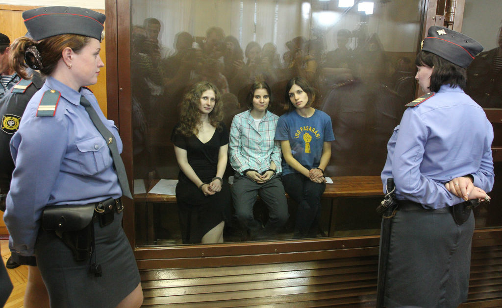 Members of the all-girl punk band 'Pussy Riot' Nadezhda Tolokonnikova (R), Maria Alyokhina (L) and Yekaterina Samutsevich sit in a glass-walled cage after being sentenced in Moscow on Agust 17, 2012.