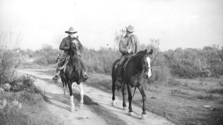 The way we picture them. In an undated photo, two sheriff's deputies ride down a dirt road on horseback through the natural scrub landscape that surrounds the El Monte hog farm after the flood.