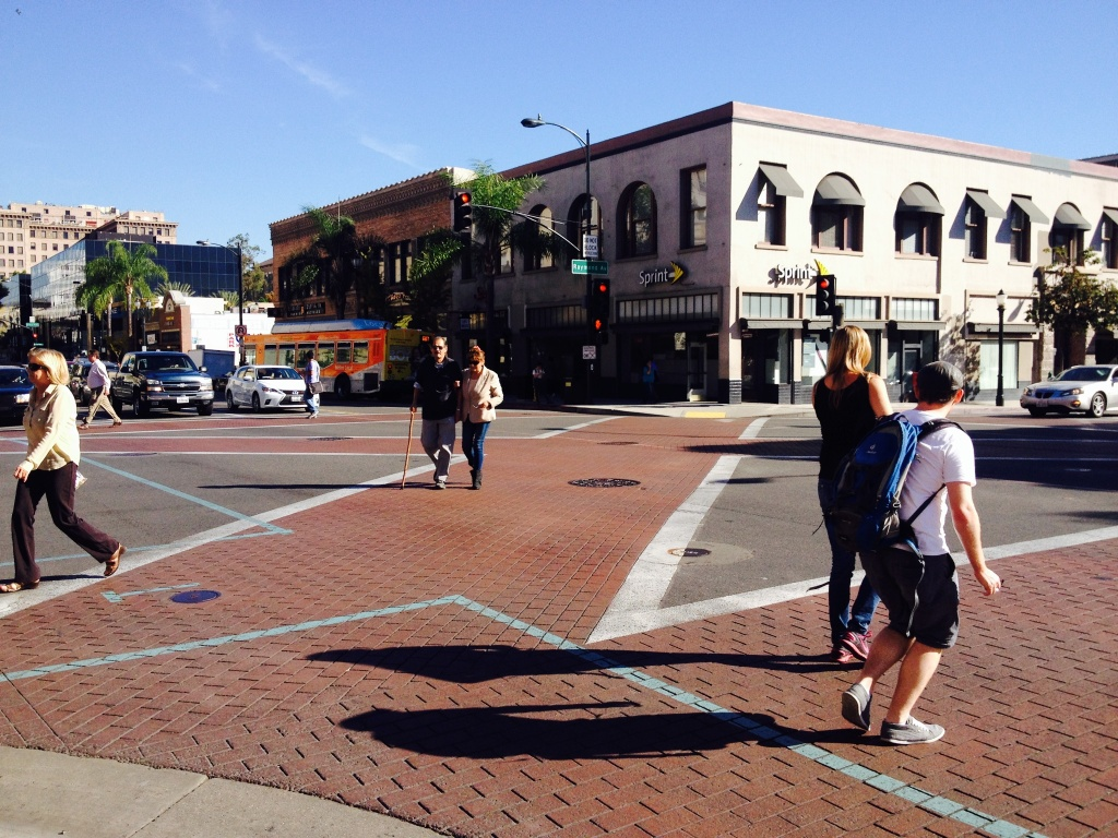 Pedestrians take the diagonal crosswalk on Colorado Boulevard and Raymond Avenue in Old Town Pasadena.