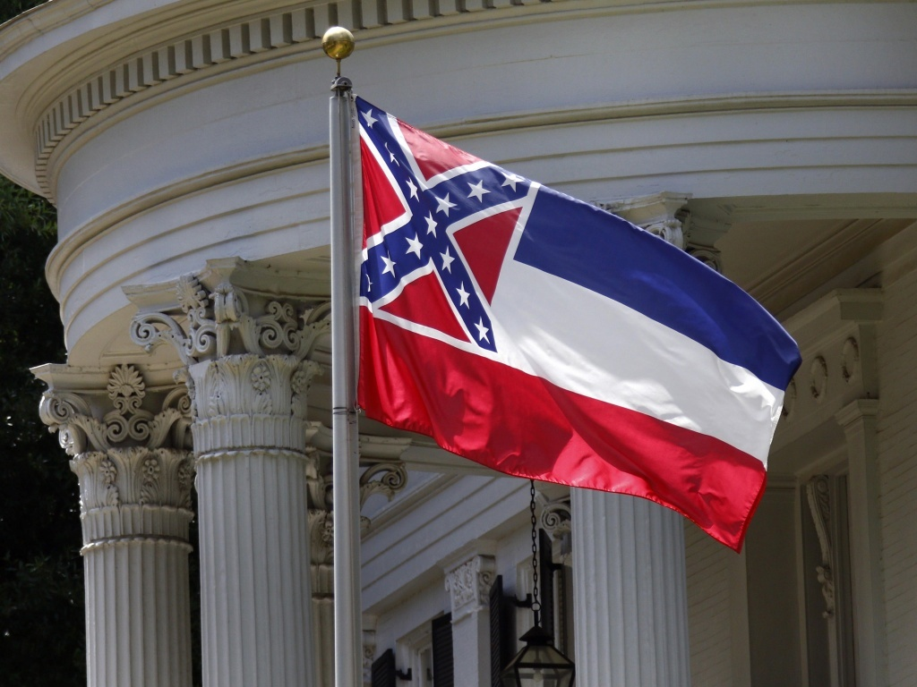 The state flag of Mississippi is unfurled against the front of the Governor's Mansion in Jackson, Miss., on Tuesday. The flag has been the center of renewed controversy since last week's racially motivated shooting of nine parishioners at a black church in South Carolina.