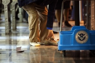 A passenger removes their shoes before passing through the passenger security checkpoint at John F. Kennedy International Airport in New York City.