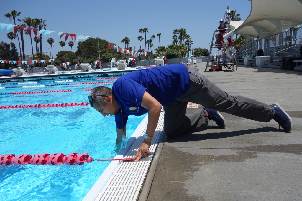 Juan Garcia of the Long Beach Environmental Health Department takes a sample of water to test for residual chlorine at Belmont Pool in Long Beach June 7, 2018. (Photo by Sharon McNary/KPCC)