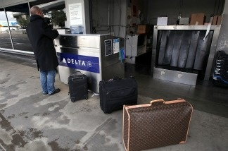 A Delta Air Lines customer checks in curbside in San Francisco. In New York City, international passengers arriving on a Delta flight from London on Monday were accidentally let out of the airport without going through immigration and customs.
