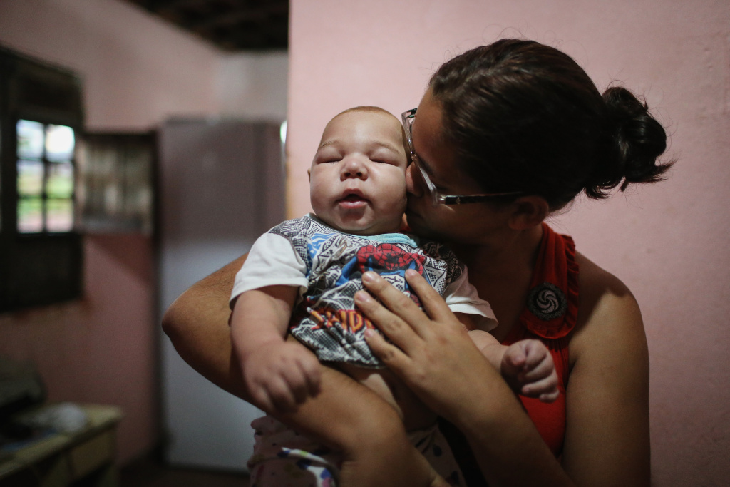 RECIFE, BRAZIL - JANUARY 29:  David Henrique Ferreira, 5 months, who was born with microcephaly, is kissed by his mother Mylene Helena Ferreira on January 29, 2016 in Recife, Pernambuco state, Brazil. In the last four months, authorities have recorded around 4,000 cases in Brazil in which the mosquito-borne Zika virus may have led to microcephaly in infants. The ailment results in an abnormally small head in newborns and is associated with various disorders including decreased brain development. According to the World Health Organization (WHO), the Zika virus outbreak is likely to spread throughout nearly all the Americas.  (Photo by Mario Tama/Getty Images)