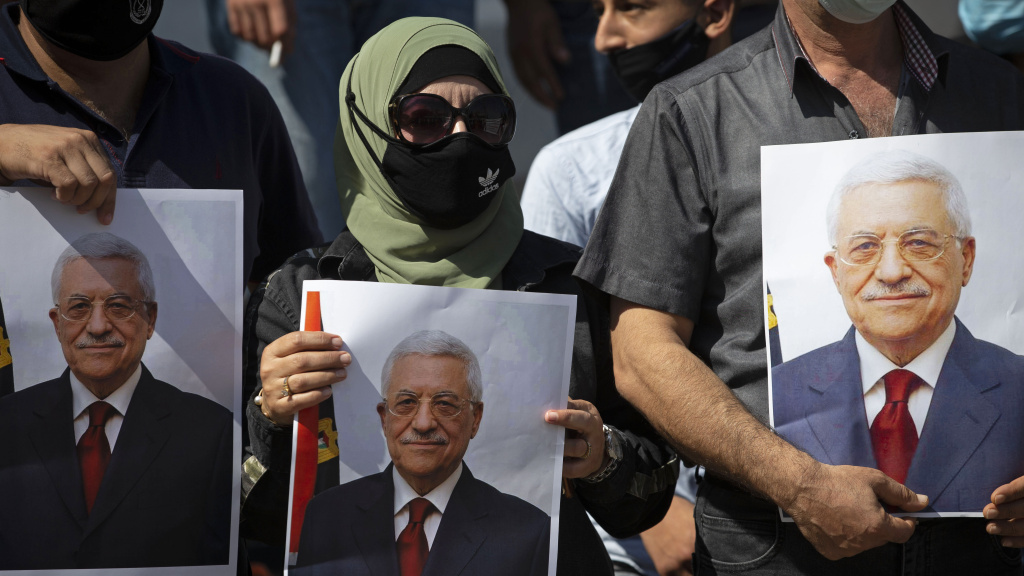 Palestinians wearing protective face masks amid the coronavirus pandemic hold pictures of Palestinian Authority President Mahmoud Abbas during a September rally in the West Bank town of Tubas.