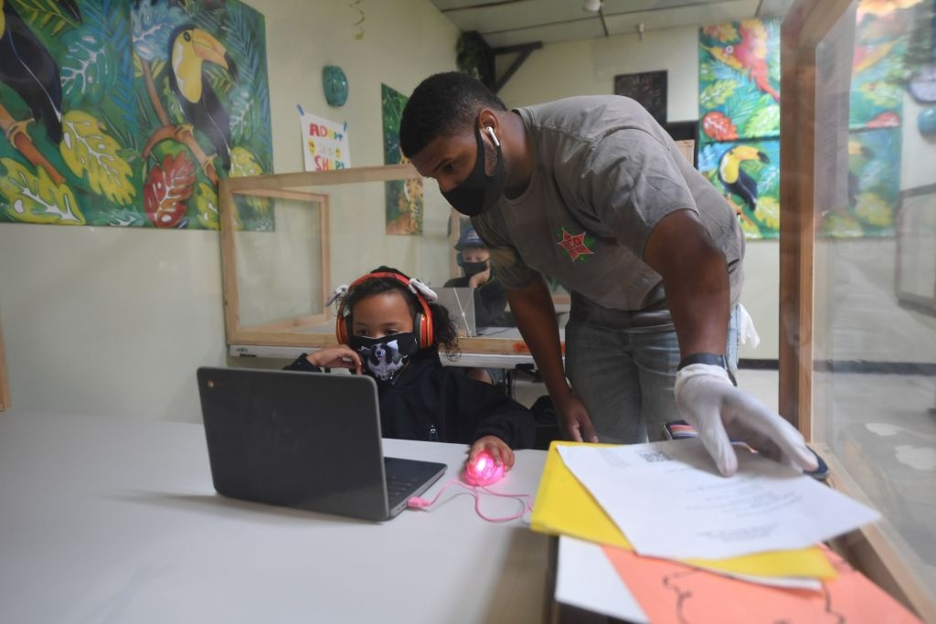 An instructor helps a student with her online school lesson at a desk separated from others by plastic barriers at STAR Eco Station Tutoring & Enrichment Center on September 10, 2020 in Culver City, California.