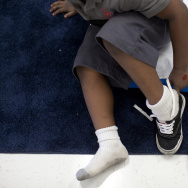 File: A young boy at a Children's Institute facility in Imperial Gardens in Watts puts on his shoes before taking a nap. The program offers a safe haven for children who may live in housing projects known for drug activity and violence.