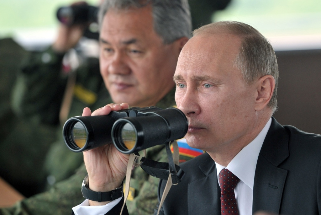In this Tuesday, July 16, 2013 file photo Russian President Vladimir Putin, flanked by Defense Minister Sergei Shoigu, uses binocular as he watches military exercise near Yuzhno-Sakhalinsk, on Sakhalin Island, Russia. President Vladimir Putin on Wednesday, Feb. 26, 2014, ordered massive exercises involving most of its military units in western Russia amid tensions in Ukraine.