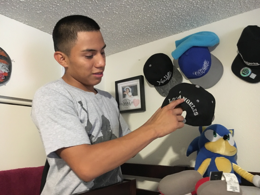 Luis Gonzalez, 16, shows off his baseball hat collection in his room. He was granted asylum, along with his brother, Alejandro, in 2016.