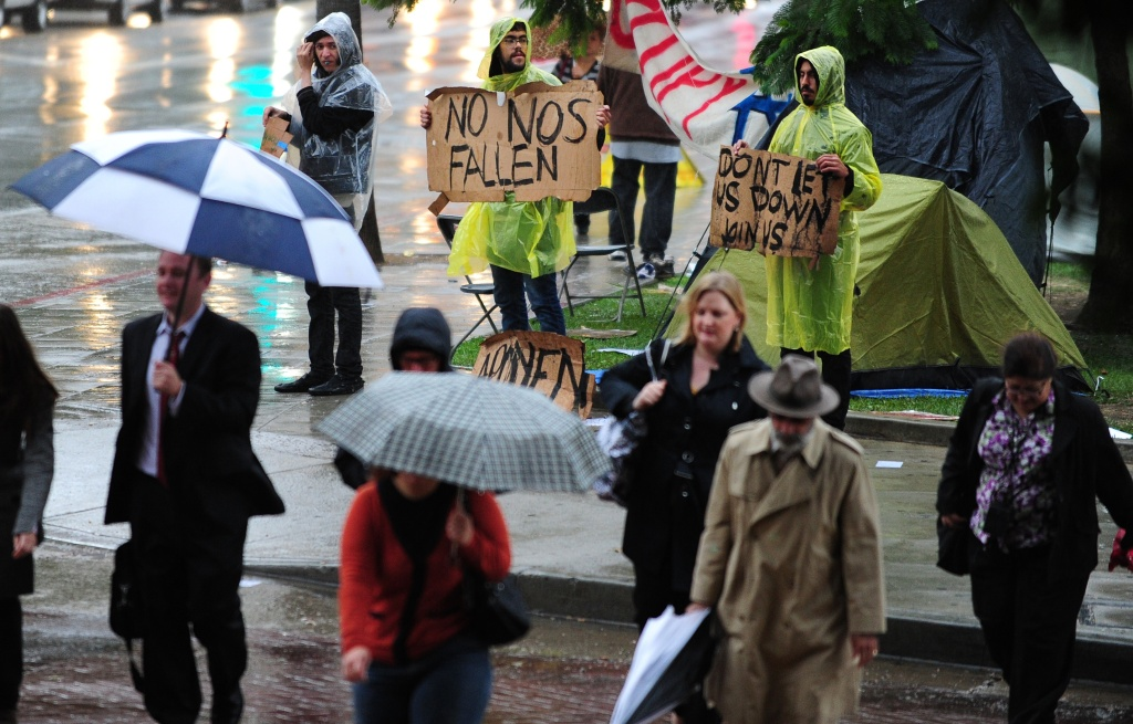 Activists protesting corporate greed who have been camped out in front of City Hall in downtown Los Angeles in solidarity with the Occupy Wall Street movement hold placards in the rain as office workers walk past on October 5, 2011. According to the private payrolls firm ADP, US companies added a meager 91,000 jobs last month with the number of jobs in the service and goods-producing sectors rising, while manufacturing jobs ebbed.