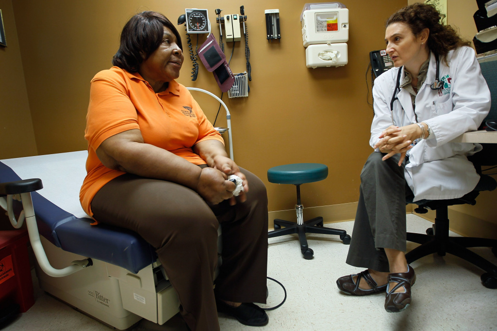 Brenda Major (left), who said she had a pre-existing condition that made it impossible to find insurance in the days before the Affordable Care Act, is examined at a clinic in Miami.