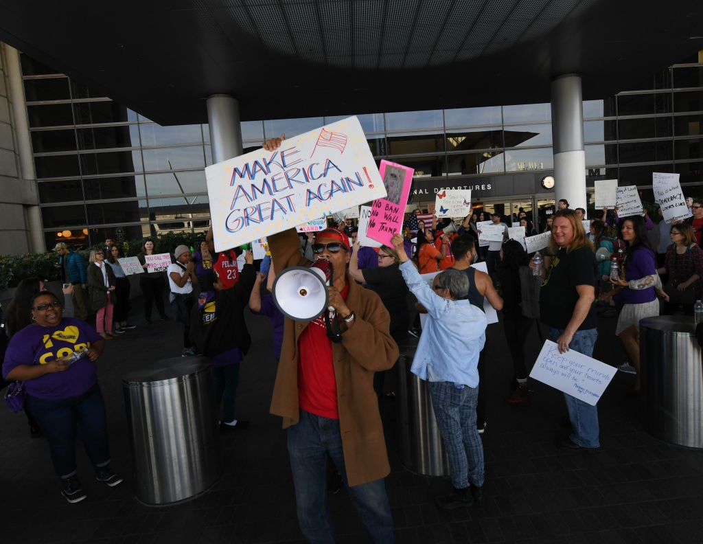 File: A pro-Trump supporter stands in front of a protest against the immigration ban  at the Los Angeles International Airport on Jan. 30, 2017.