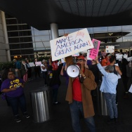 A pro-Trump supporter stands in front of a protest against the immigration ban  at the Los Angeles International Airport, California on January 30, 2017.
