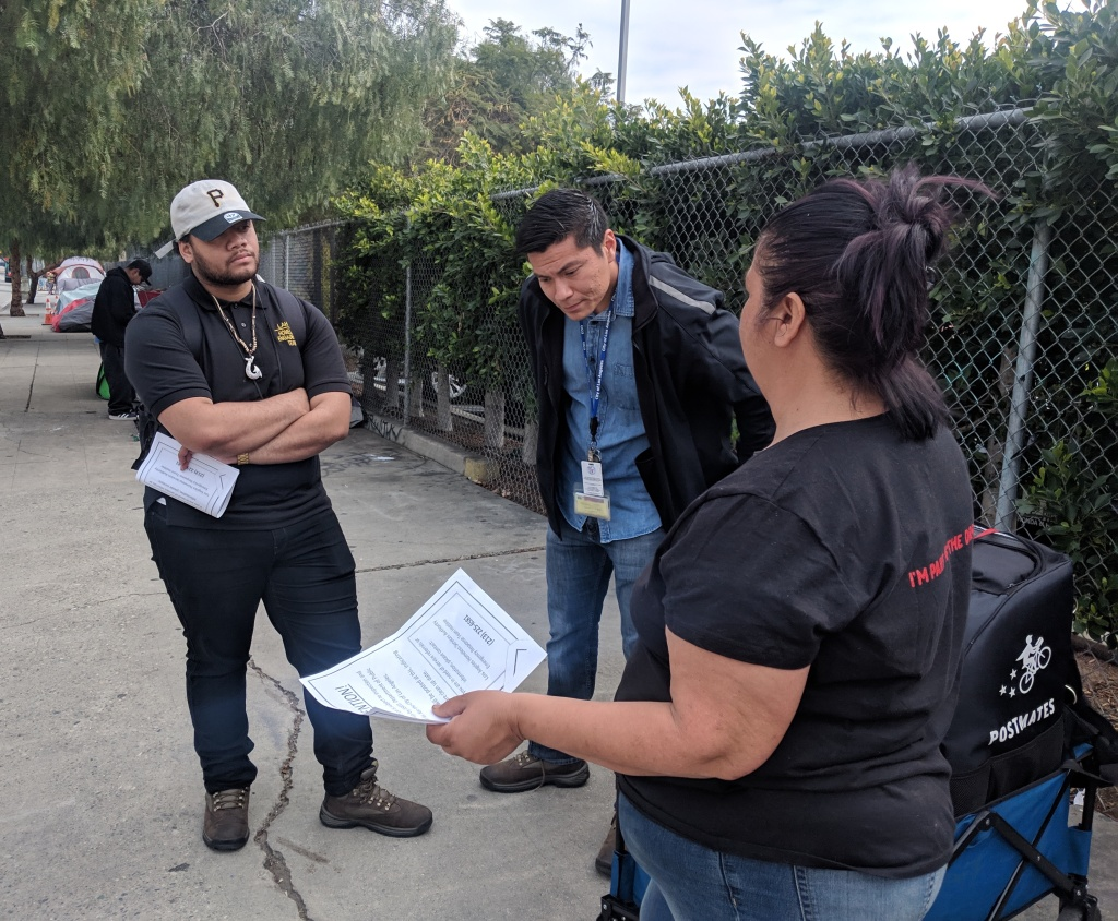 With a bridge home nearby, two outreach workers (left) listen to a woman on the streets of downtown LA, alerting her to a clean-up and inspection of those living on the sidewalks nearby