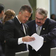 "In this Sept. 12, 2013 file photo, Republican Assembly members Travis Allen, of Huntington Beach, left, and Dan Logue, of Marysville, look over some papers during a legislative session in Sacramento, Calif. Allen recently wrote a provocative opinion piece criticizing a new law aimed at treating child sex workers as victims, writing ""teenage girls (and boys) ... will soon be free to have sex in exchange for money."""